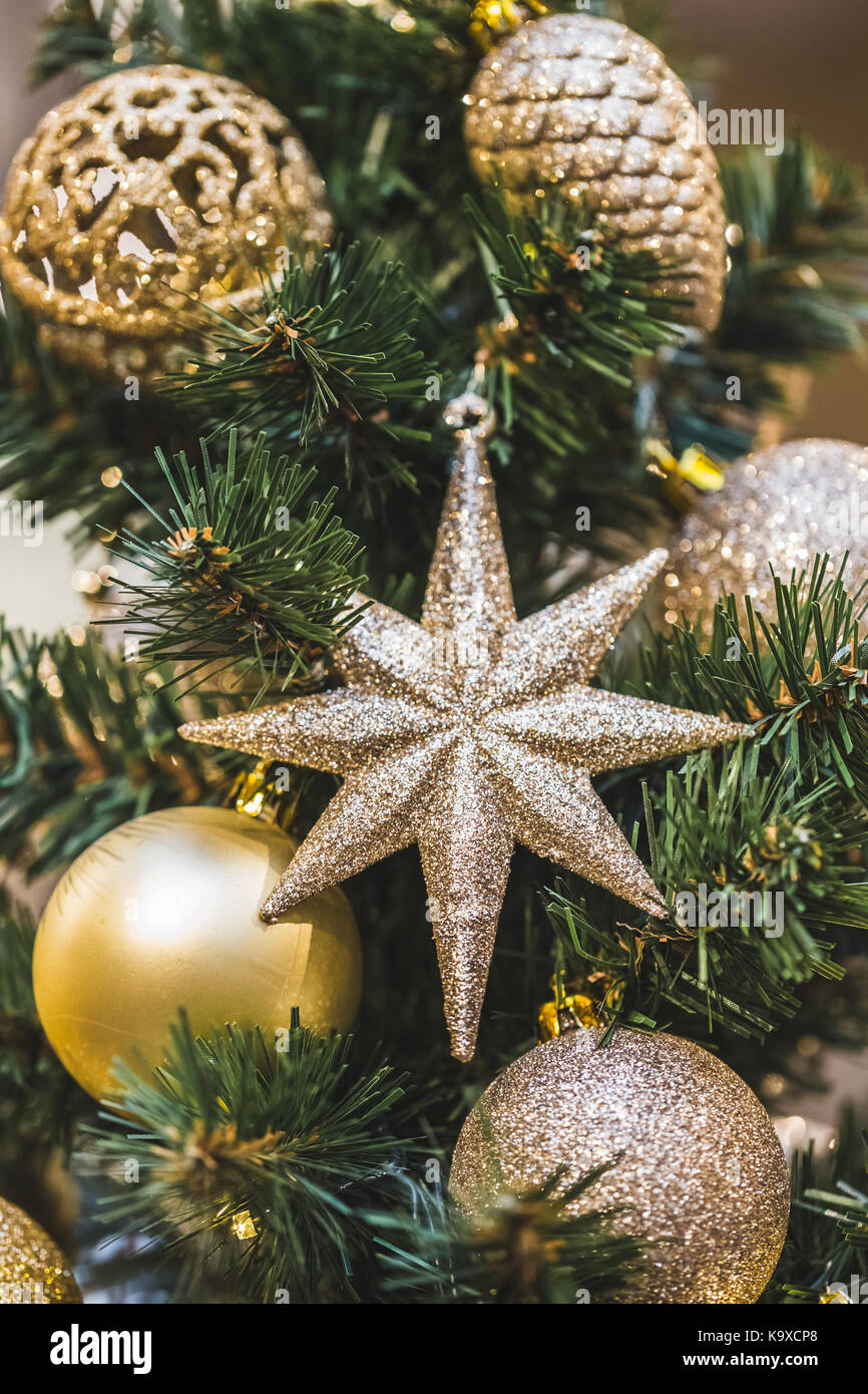 Christmas tree decorations in gold tones with lots of beautiful shiny balls and stars - Stock Image