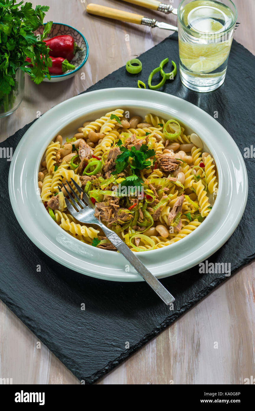 Pasta with tuna, white beans and leeks garnished with fresh parsley - Stock Image