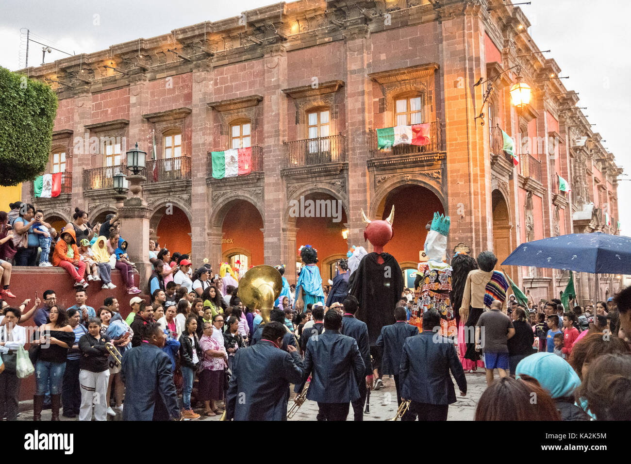 A marching band follows a parade of giant paper-mache puppets called mojigangas in a procession through the city - Stock Image