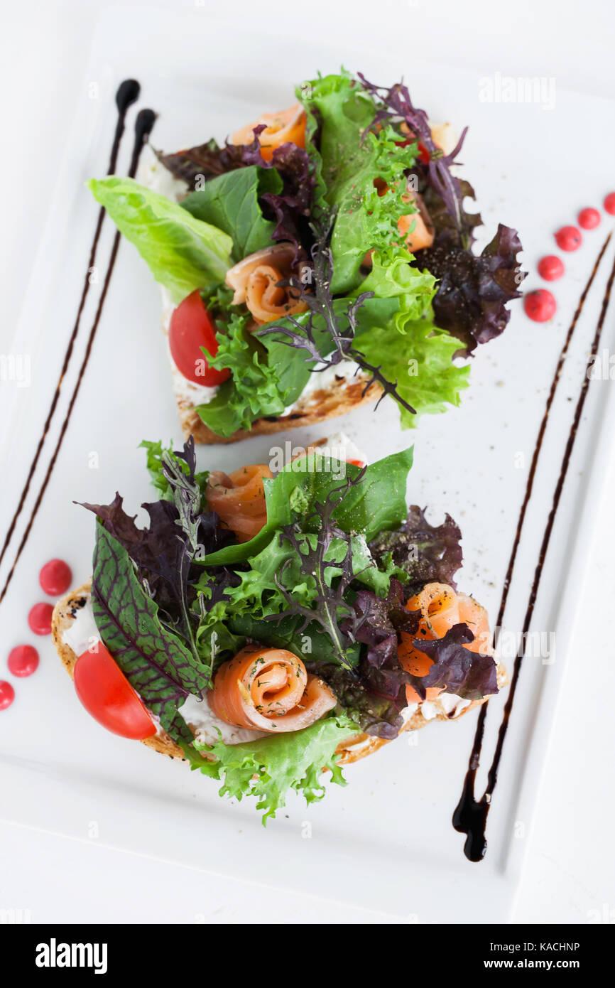 Salad with arugula, tomatoes and salmon - Stock Image