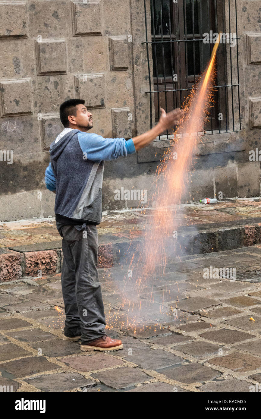 A fireworks worker sets off a bottle rocket ahead of a procession through the historic city during the week long - Stock Image
