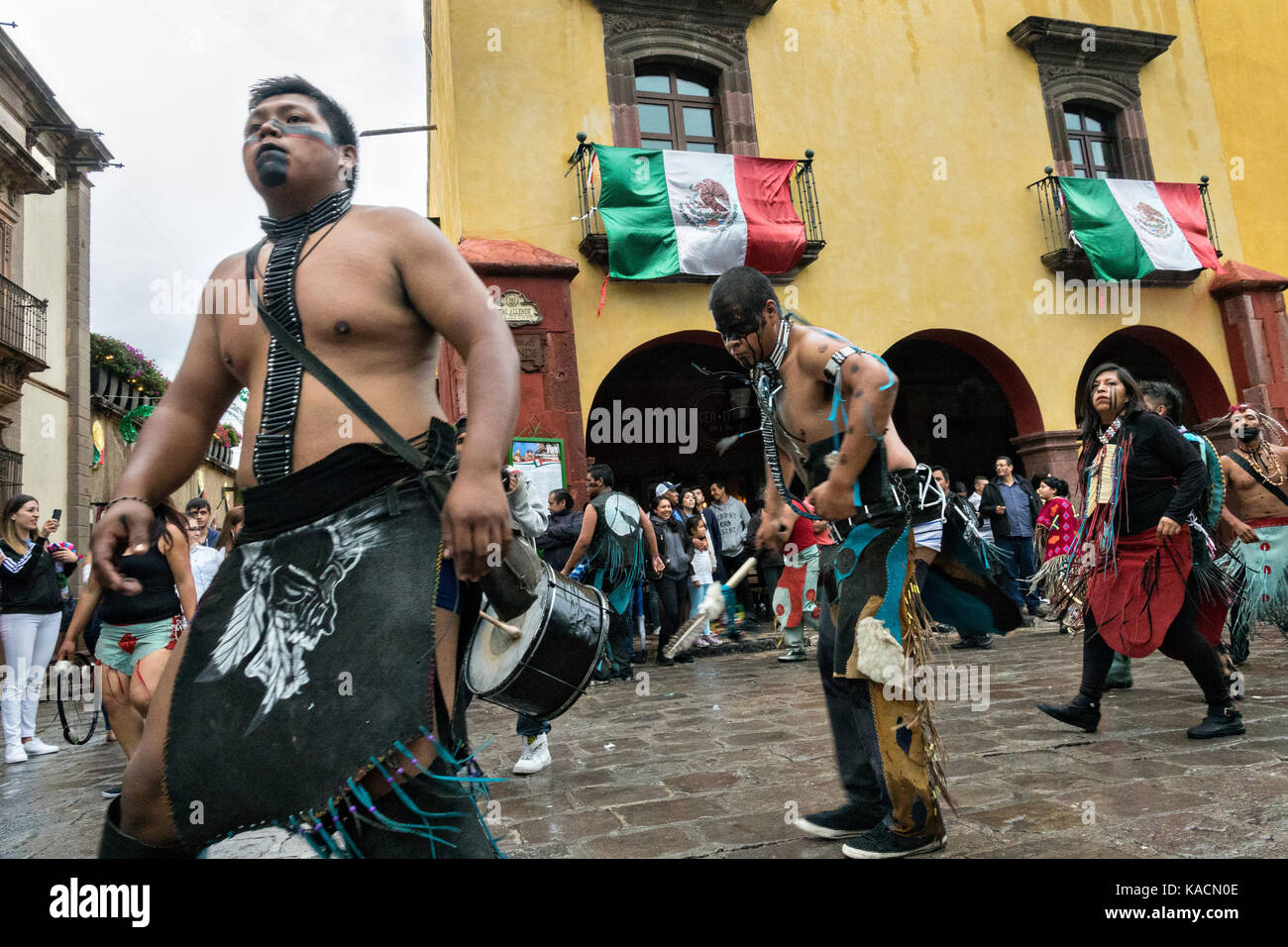 Aztec Indians dance in a procession through the Jardin Allende during the week long fiesta of the patron saint Saint - Stock Image