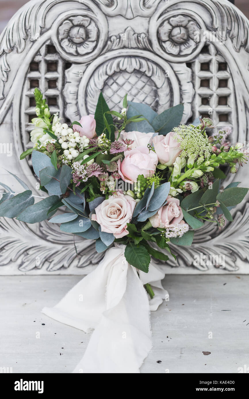 Delicate bride's bouquet with roses and peonies on a white vintage marble bench - Stock Image