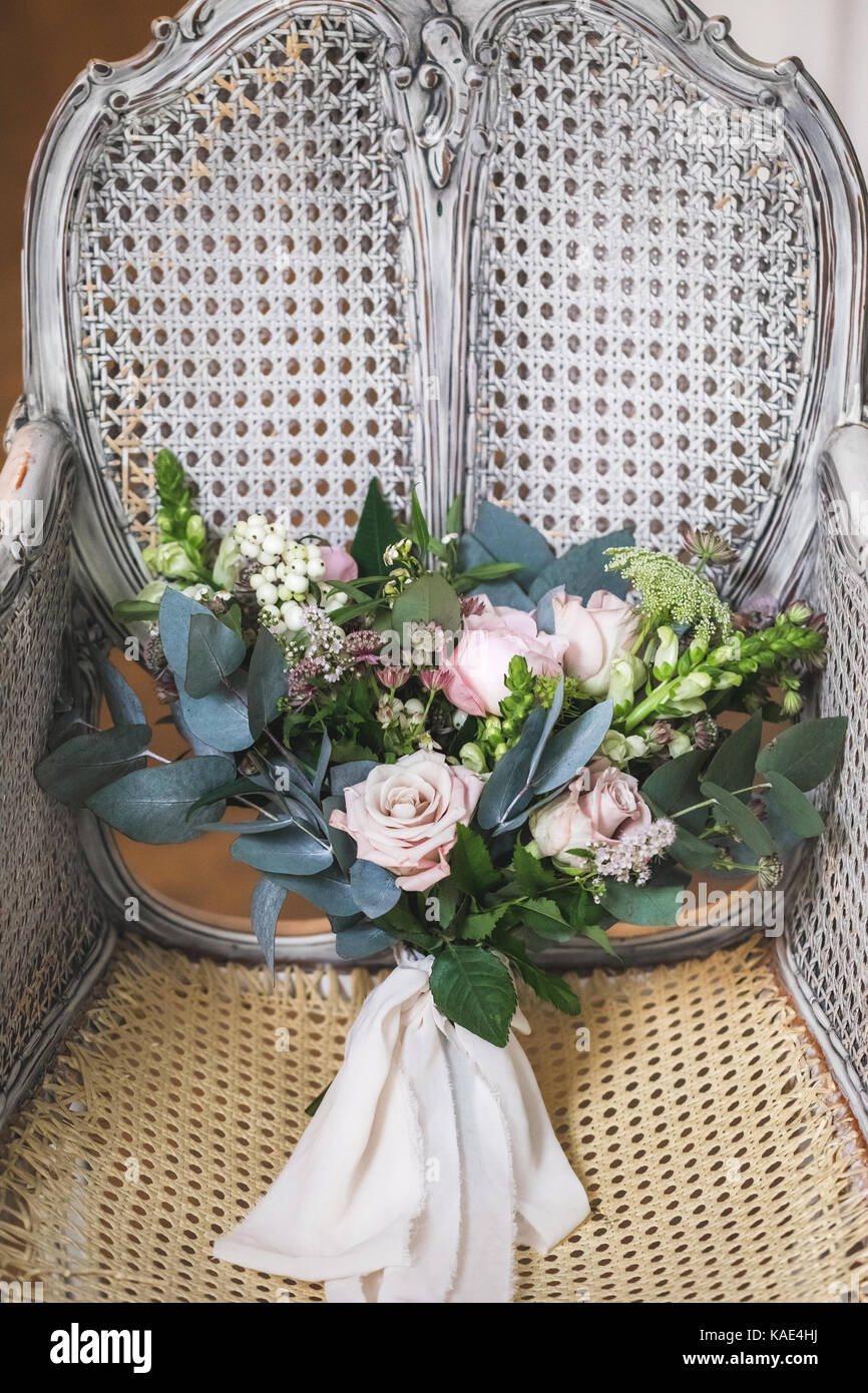 Bridal bouquet on vintage white wooden cane-chair - Stock Image