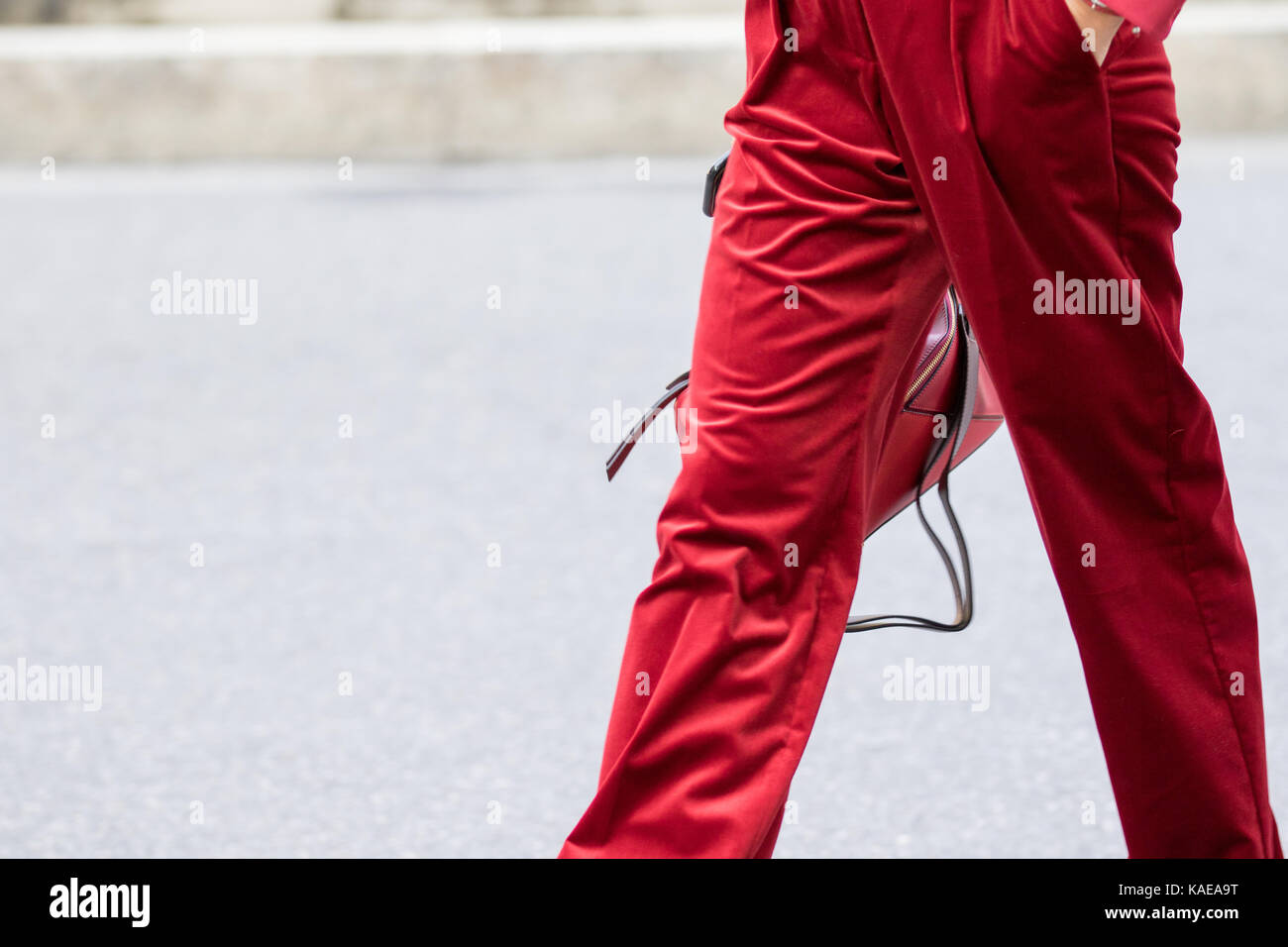 Milan, Italy - September 22, 2017: Model wearing a pair of red pants and red purse during the Armani parade, photographed - Stock Image