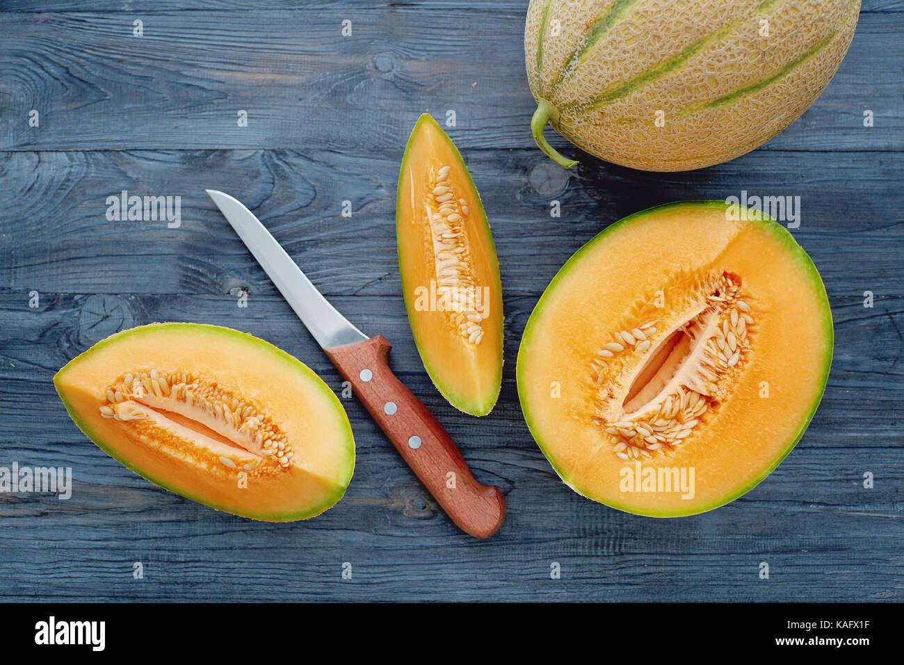 Fresh cantaloupe cut into pieces on wooden table. - Stock Image