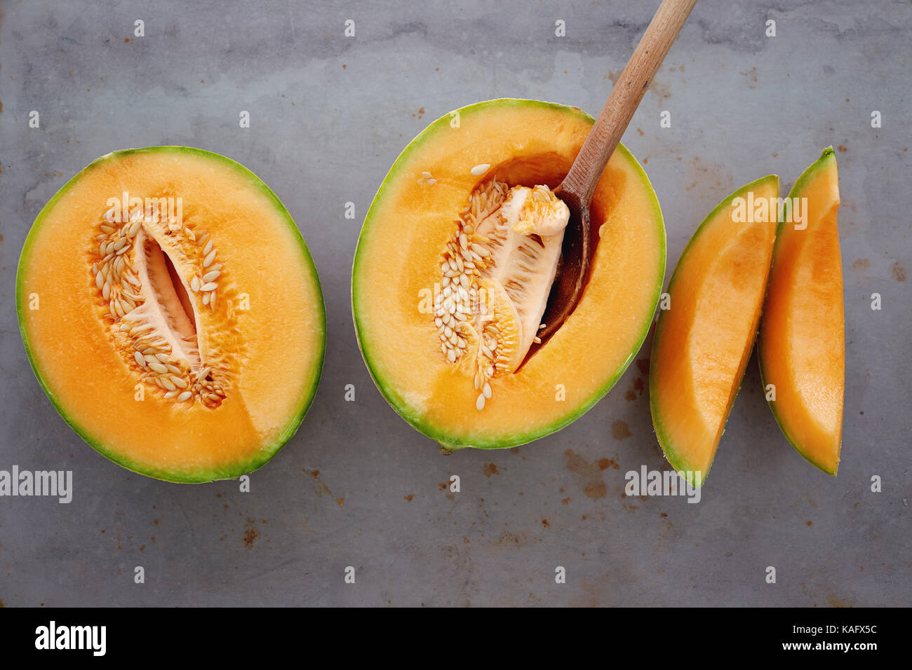 Fresh cantaloupe cut into pieces. Half cut of ripe cantaloupe melon with spoon. - Stock Image