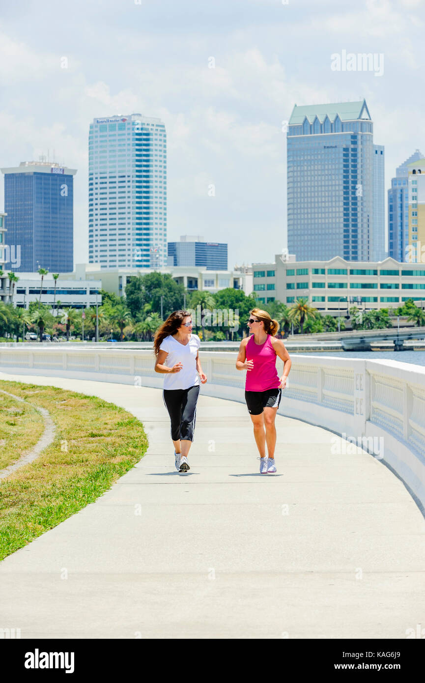 Two women jogging along Bayshore Boulevard with the downtown Tampa, Florida, USA skyline in the background.Stock Photo
