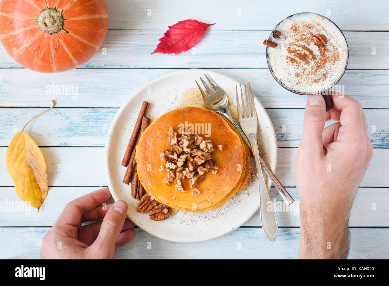 Pumpkin pancakes with pecan nuts, maple syrup, cream and cinnamon and cup of pumpkin spice latte. Person eating - Stock Image