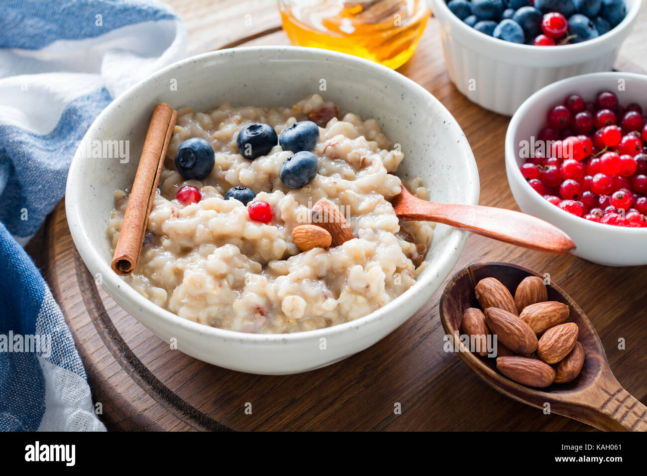 Oatmeal porridge with blueberries, almonds and currants in bowl. Healthy breakfast, dieting, balanced meal concept - Stock Image