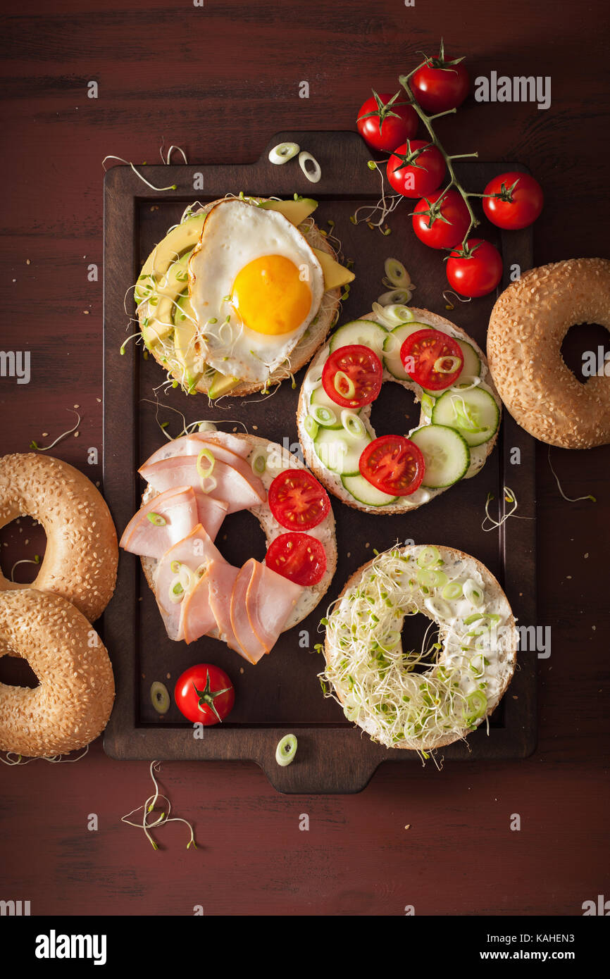 variety of sandwiches on bagels: egg, avocado, ham, tomato, soft cheese, alfalfa sprouts - Stock Image