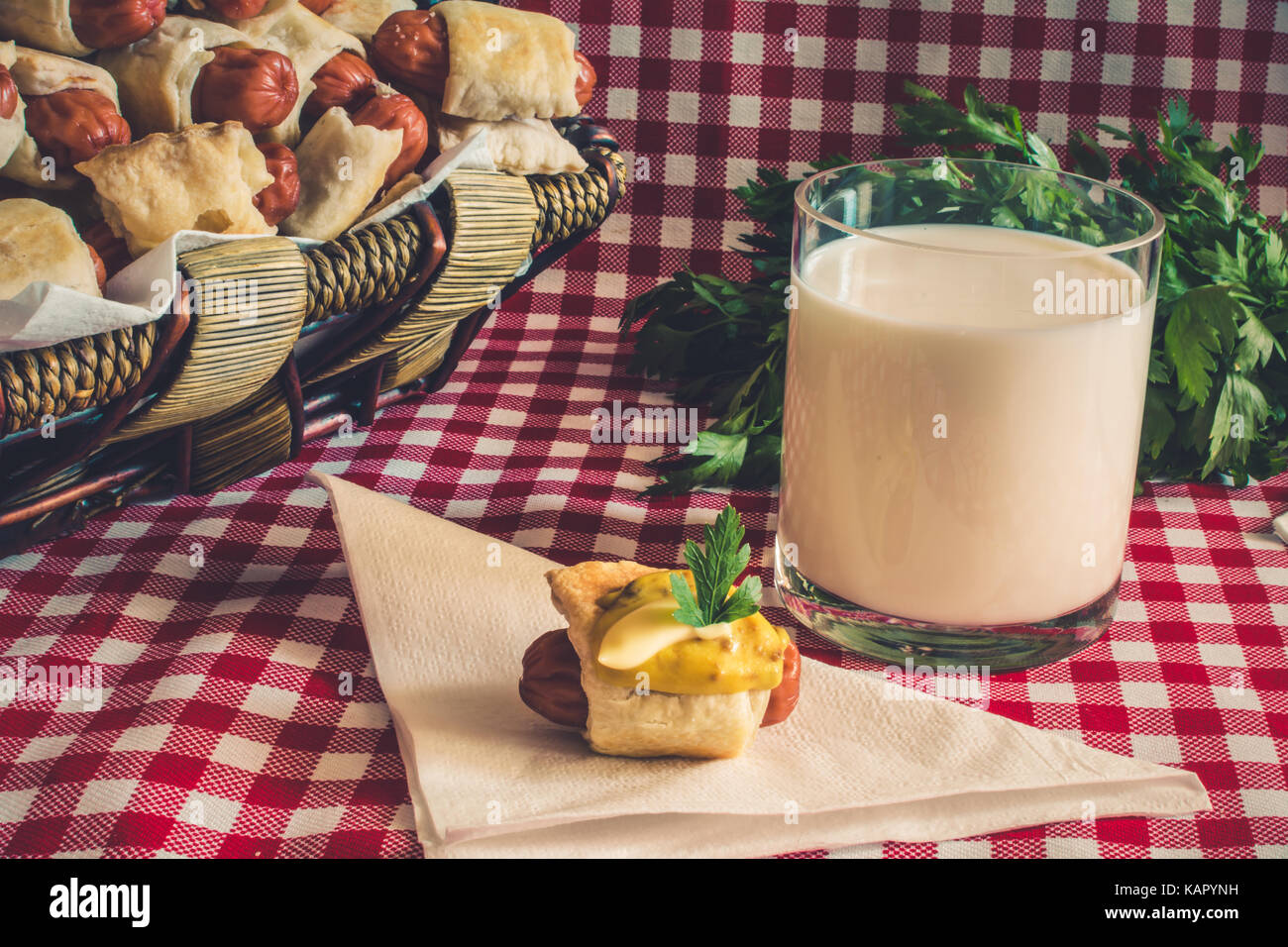 Wicker basket with artisan mini hot dogs (Sausage in the dough) with sausage on a napkin covered in mustard, mayonnaise - Stock Image