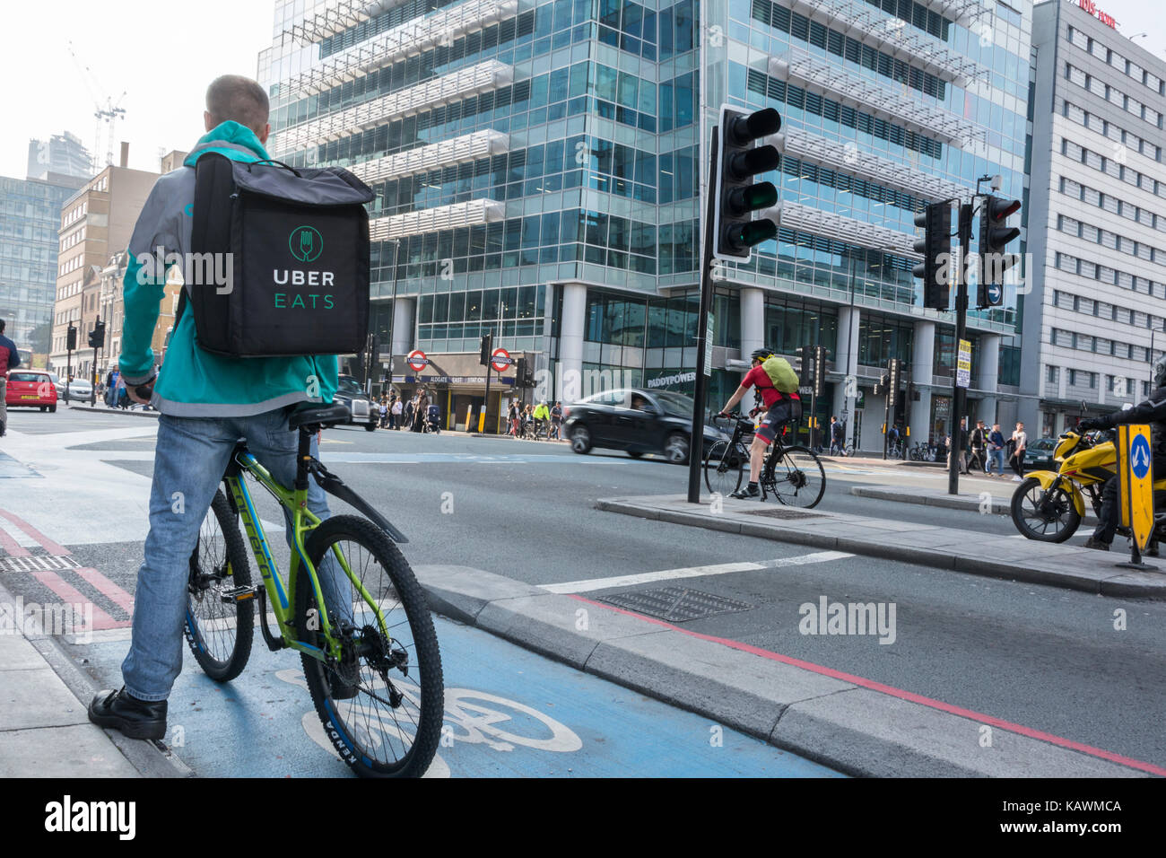 An Uber Eats delivery cyclist outside Uber Headquarters in Aldgate Tower, Whitechapel, London, UK Stock Photo