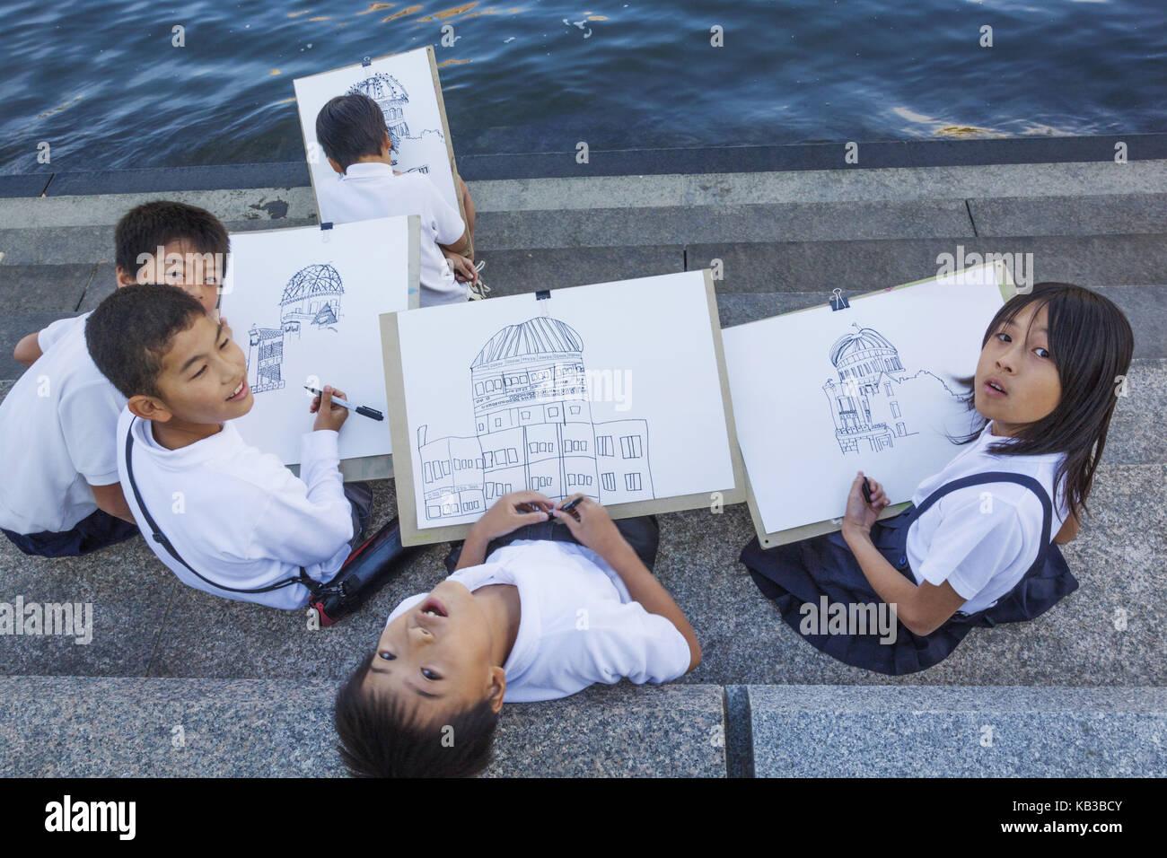 Japan, Kyushu, Hiroshima, peace park, schoolboy paint the atom bomb dome, - Stock Image
