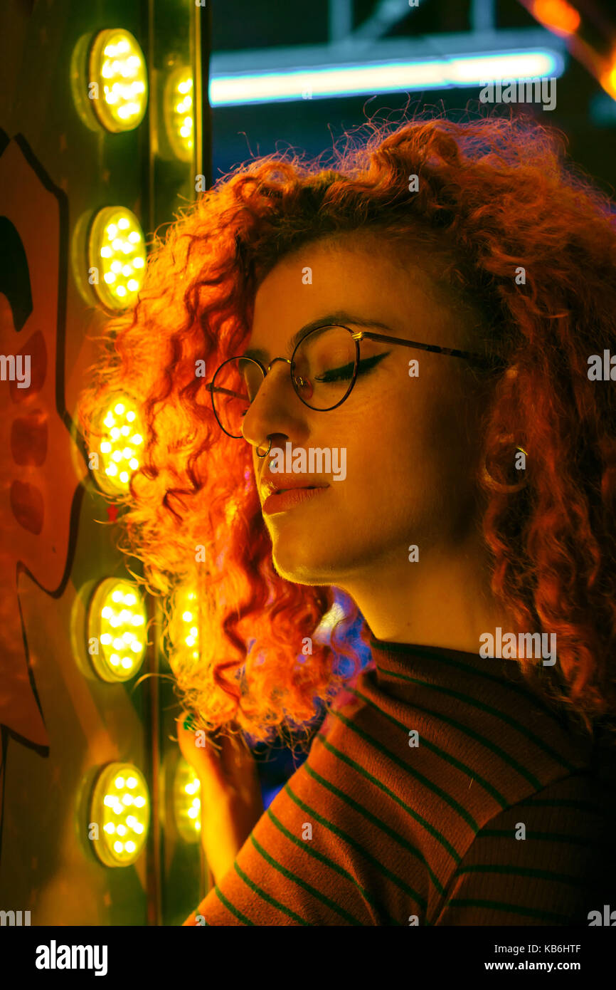 Portrait of a young woman at night illuminated with color lights - Stock Image