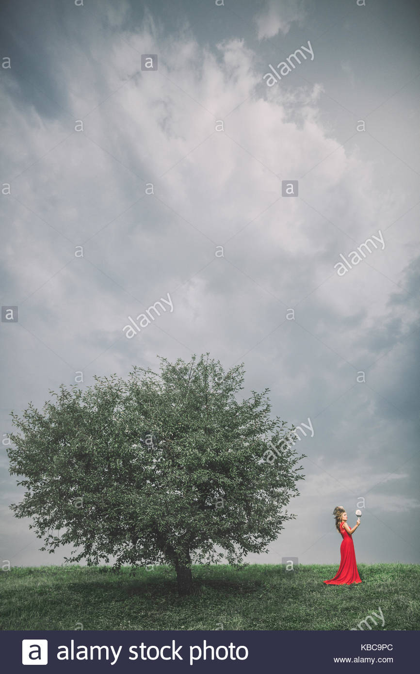 Blonde lady in a red dress by a tree, holding a mirror - Stock Image