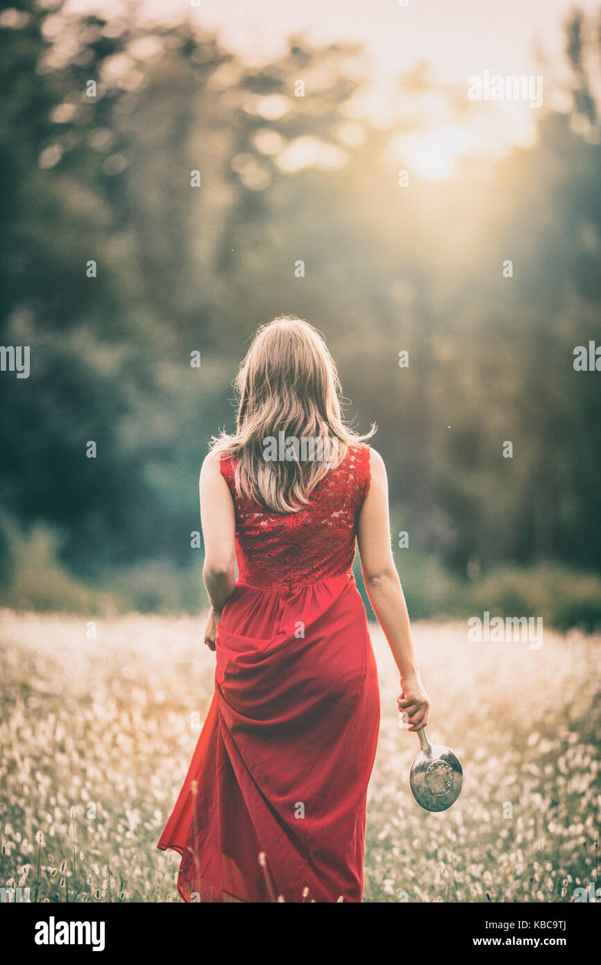girl walking in a field at sunset, in a red dress, holdinh a silver mirror - Stock Image