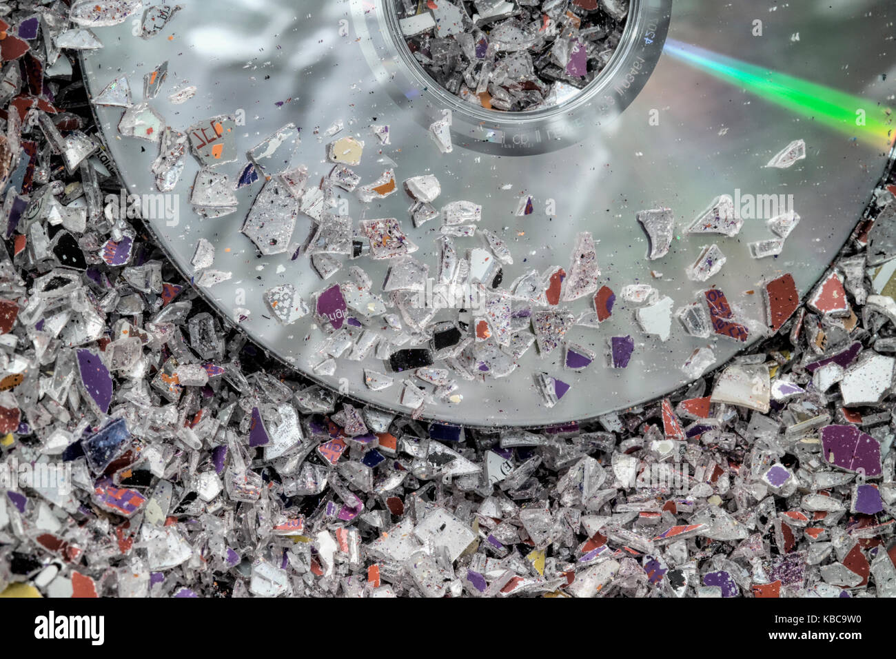 Granules of shredded plastic waste from CD & DVD manufacture. Stock Photo