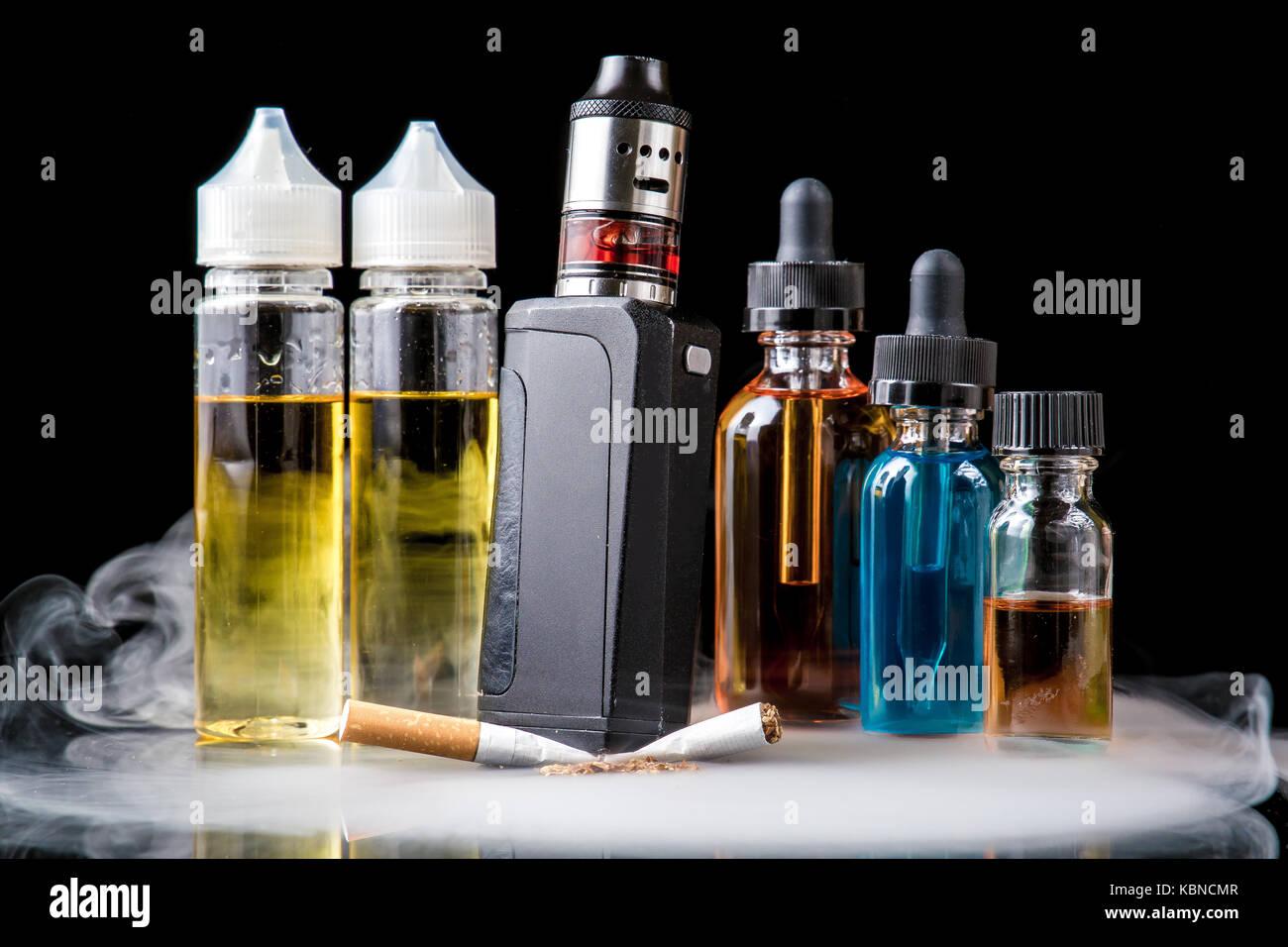 Modern vaporiser versus old tobacco cigarette in smoke - Stock Image