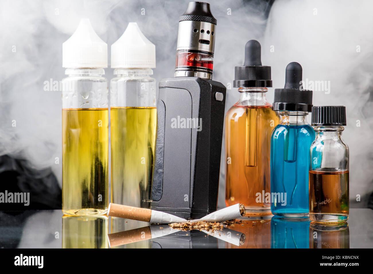 Modern vaporiser versus old tobacco cigarette in smoke cloud - Stock Image