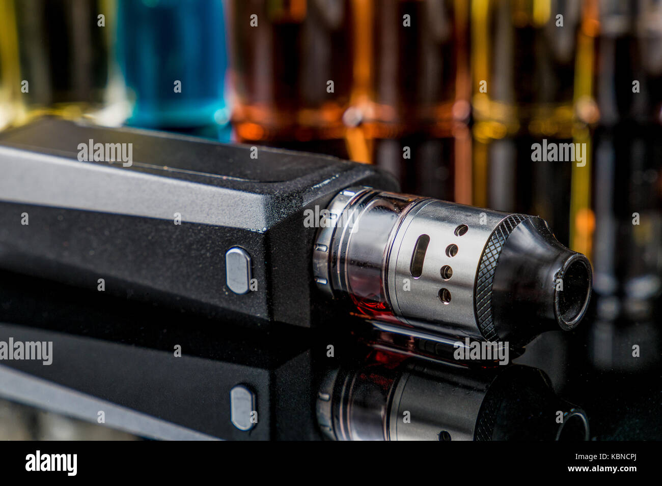 Electronic cigarette on the side with e-juice bottles in the background - Stock Image