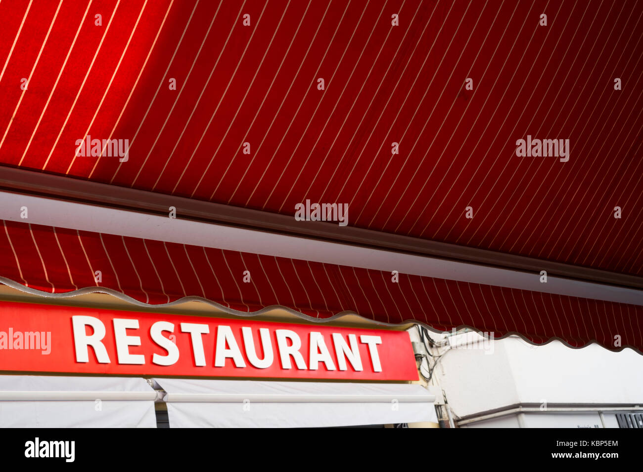 A red canopy opposite a red restaurant sign in Lloret de Mar, Spain Stock Photo