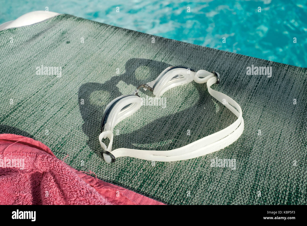 Pair of swimming goggles left on a sun lounger by a pool at Hotel Ninays in Lloret de Mar Stock Photo