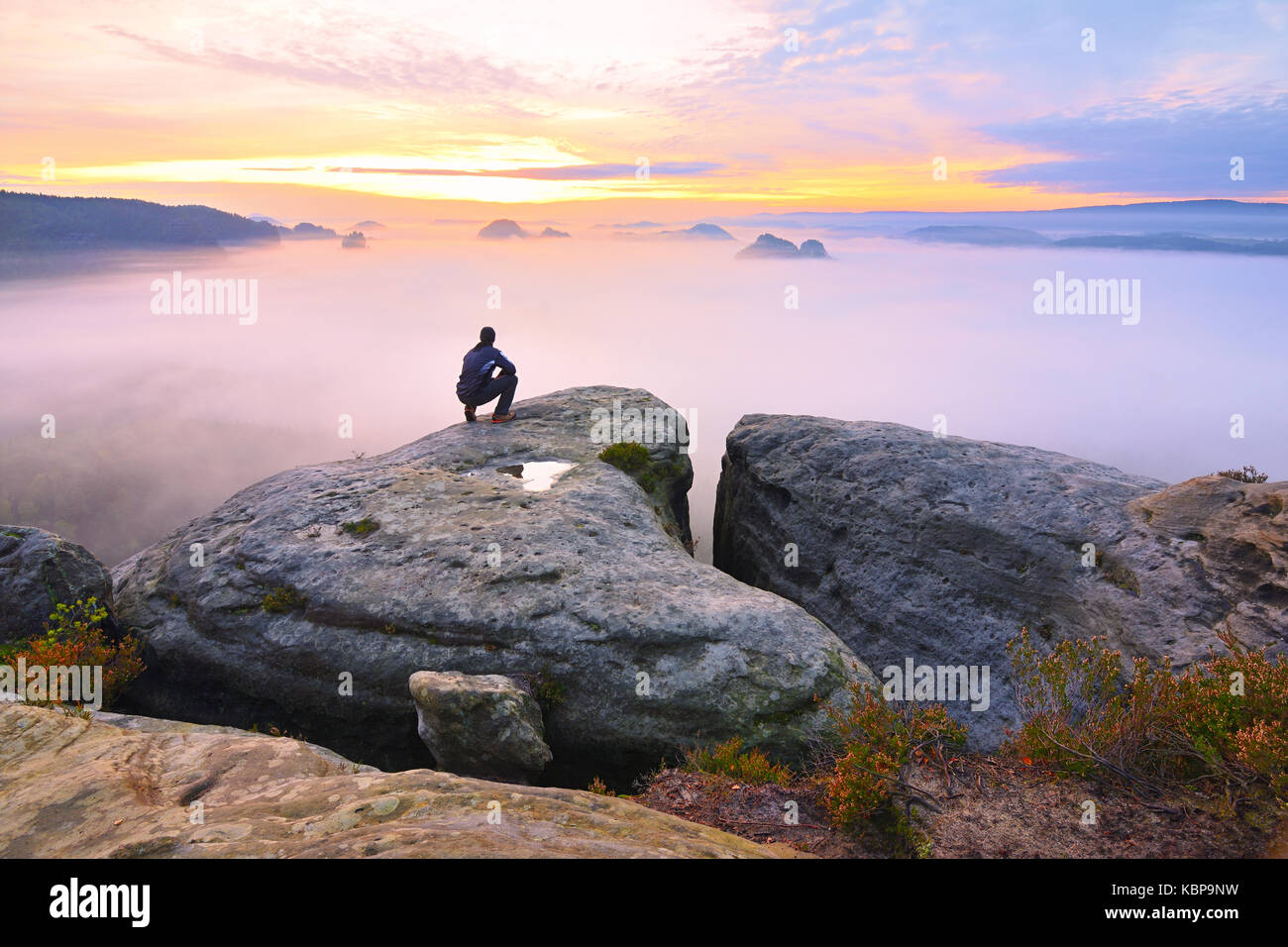 Sharp rear man silhouette on rocky peak. Satisfy hiker enjoy view. Tall man on rocky cliff watching down to landscape. - Stock Image