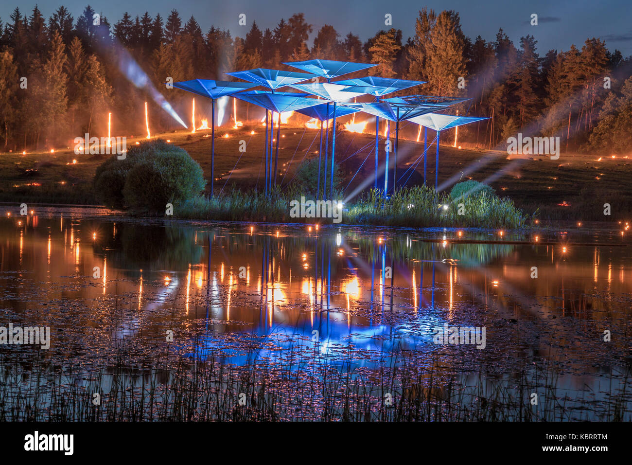Burning fire in the background with searching lights and reflection from the lake - Stock Image