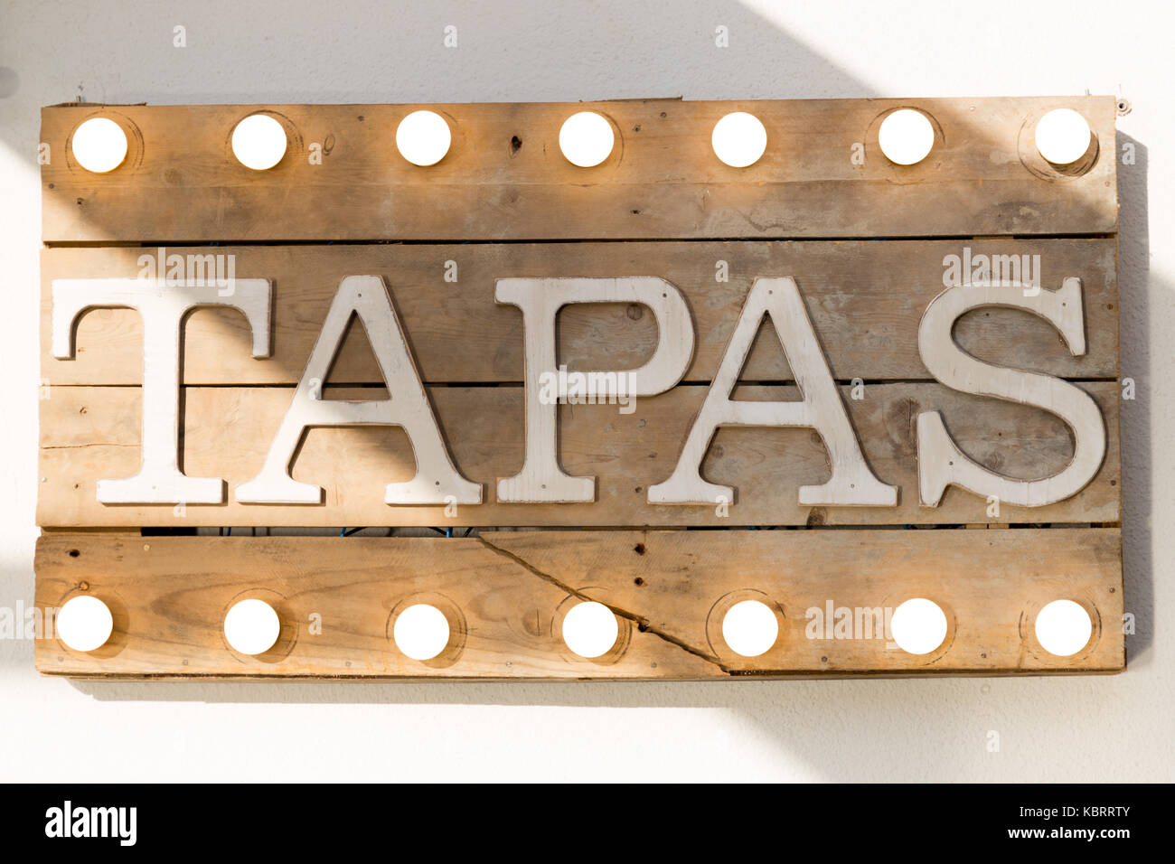 Tapas sign made of wooden planks and light bulbs on top and bottom - Stock Image