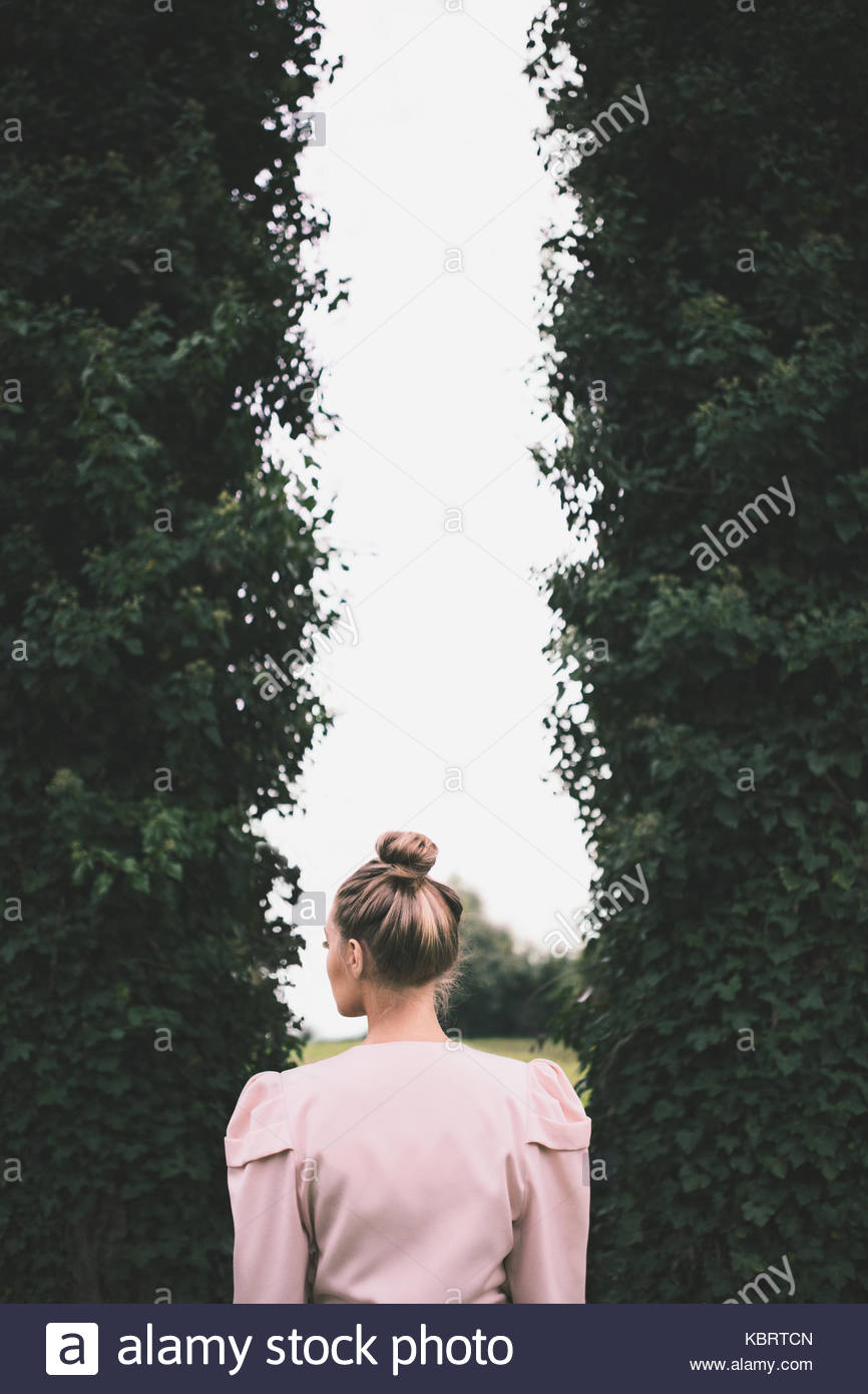 Blonde girl standing by two tall trees covered in ivy - Stock Image