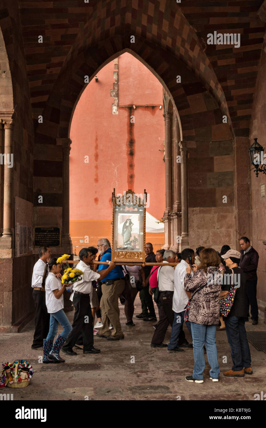 Devotees carry the statue of Saint Michael on their shoulders to the Parroquia de San Miguel Arcangel church during - Stock Image