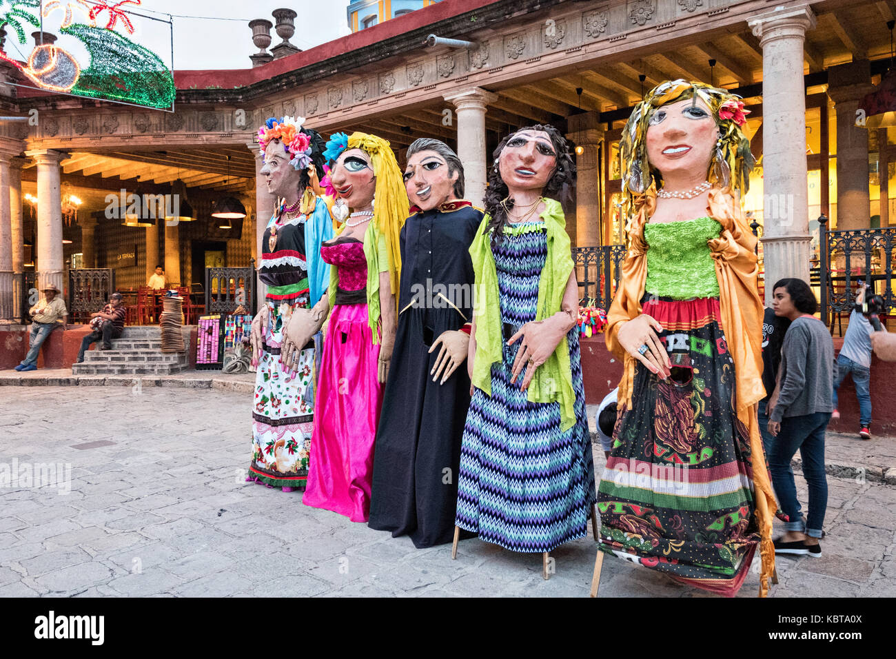 Giant paper-mache puppets called mojigangas line up for a parade during the week long fiesta of the patron saint - Stock Image