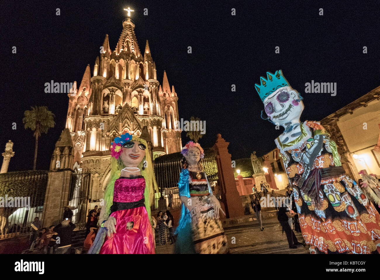 Giant paper-mache puppets called mojigangas dance past the Parroquia church during the week long fiesta of the patron - Stock Image