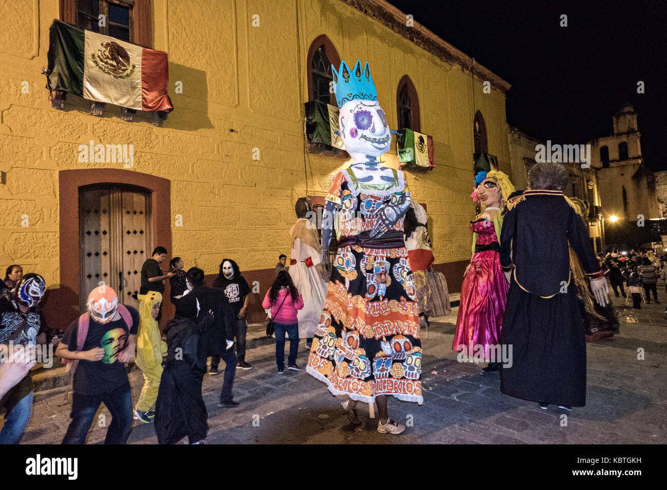 Giant paper-mache puppets called mojigangas lead a procession through the historic district during the week long - Stock Image