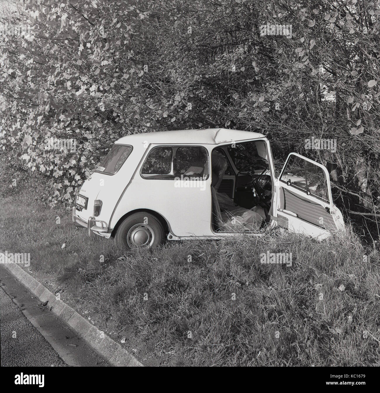 1960s, historical, a smashed Mini car following a road accident lies in a ditch beside a country road, Aylesbury, - Stock Image