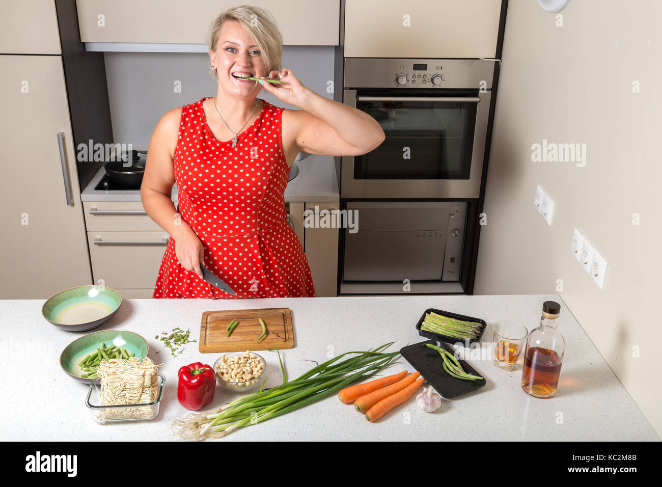 Girl biting asparagus and holding knife in other hand - Stock Image