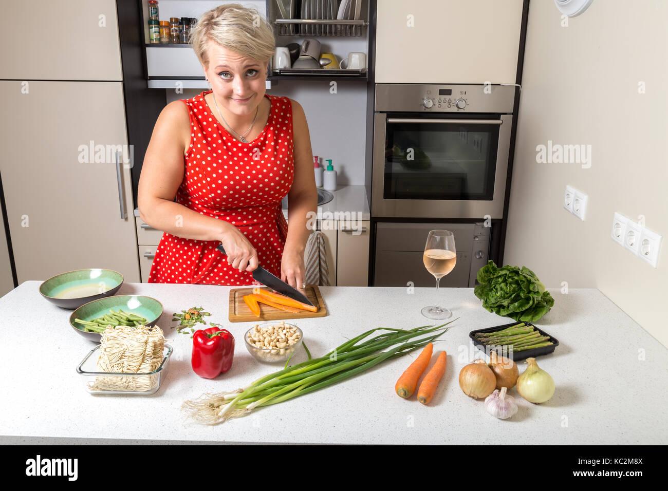 Girl smiling at camera and preparing food - Stock Image