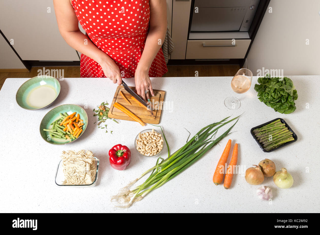 Girl cutting carrots and preparing food - Stock Image