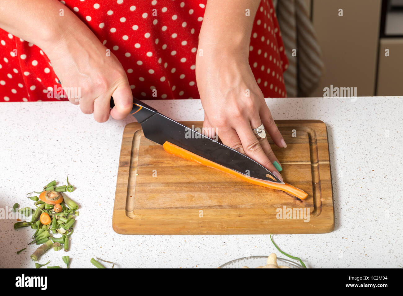 Young female close up on cutting carrot - Stock Image