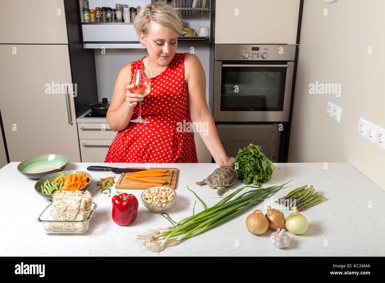 Woman observes tortoise eating on salad - Stock Image