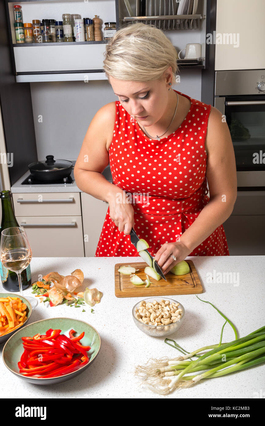 Cute girl cutting onions in red dotted dress - Stock Image