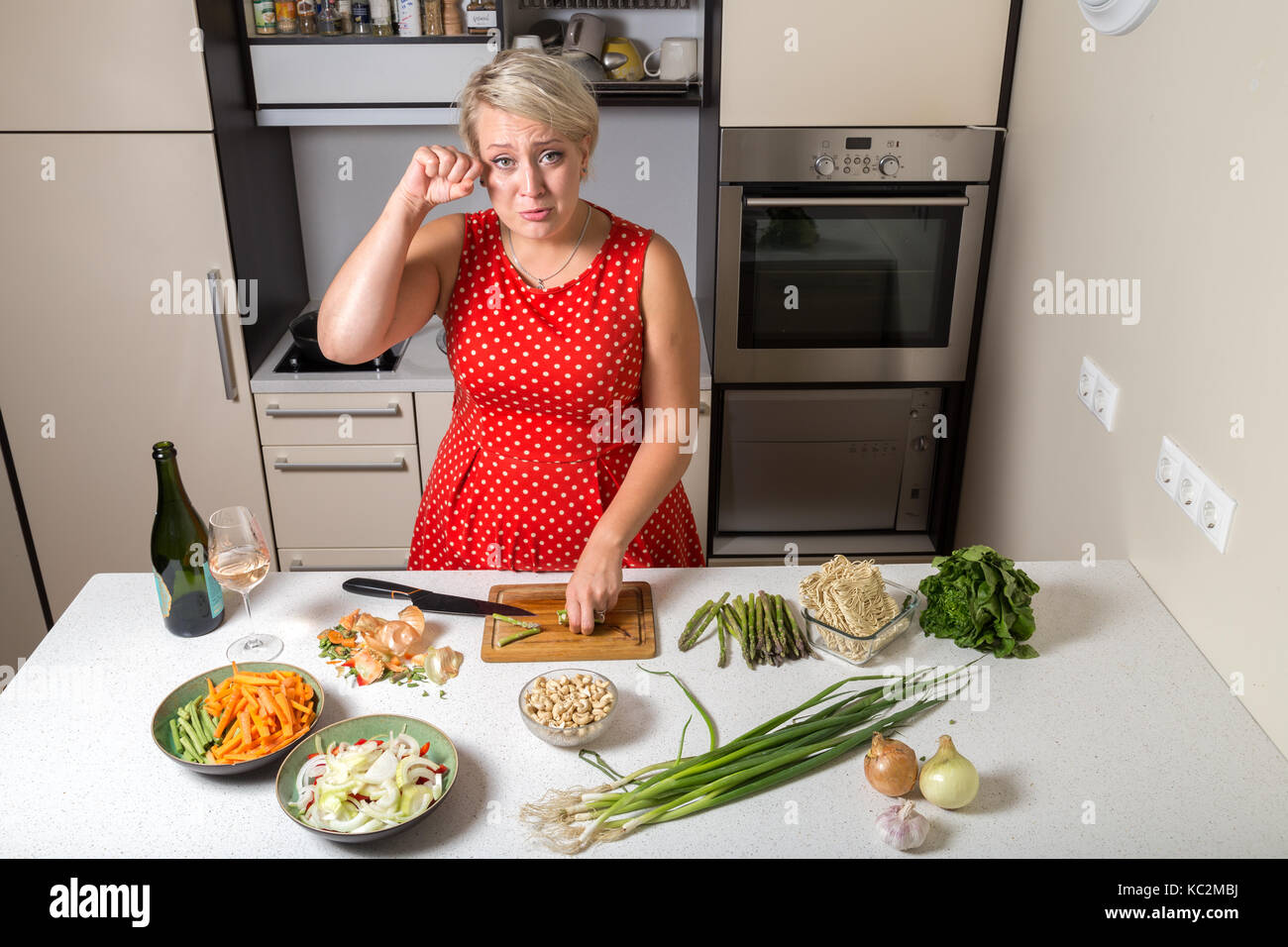 Female in kitchen cutting asparagus and rubbing her eye - Stock Image