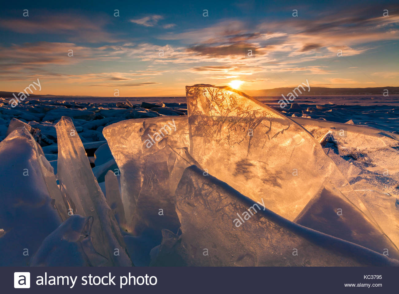 Colorful sunset over the crystal ice of Baikal lake - Stock Image