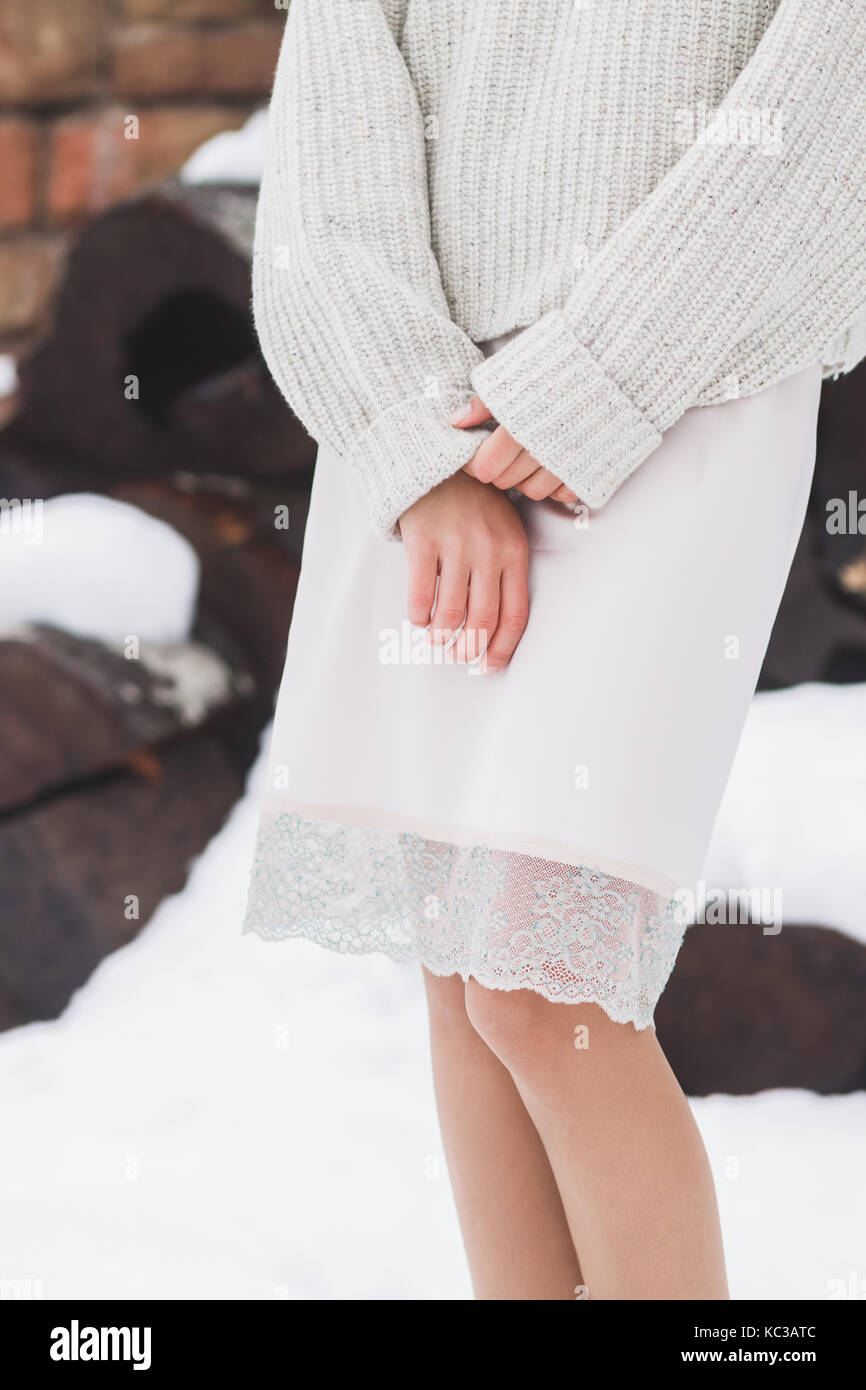Winter look, girl in warm woolen sweater and a skirt made of natural silk with lace - Stock Image