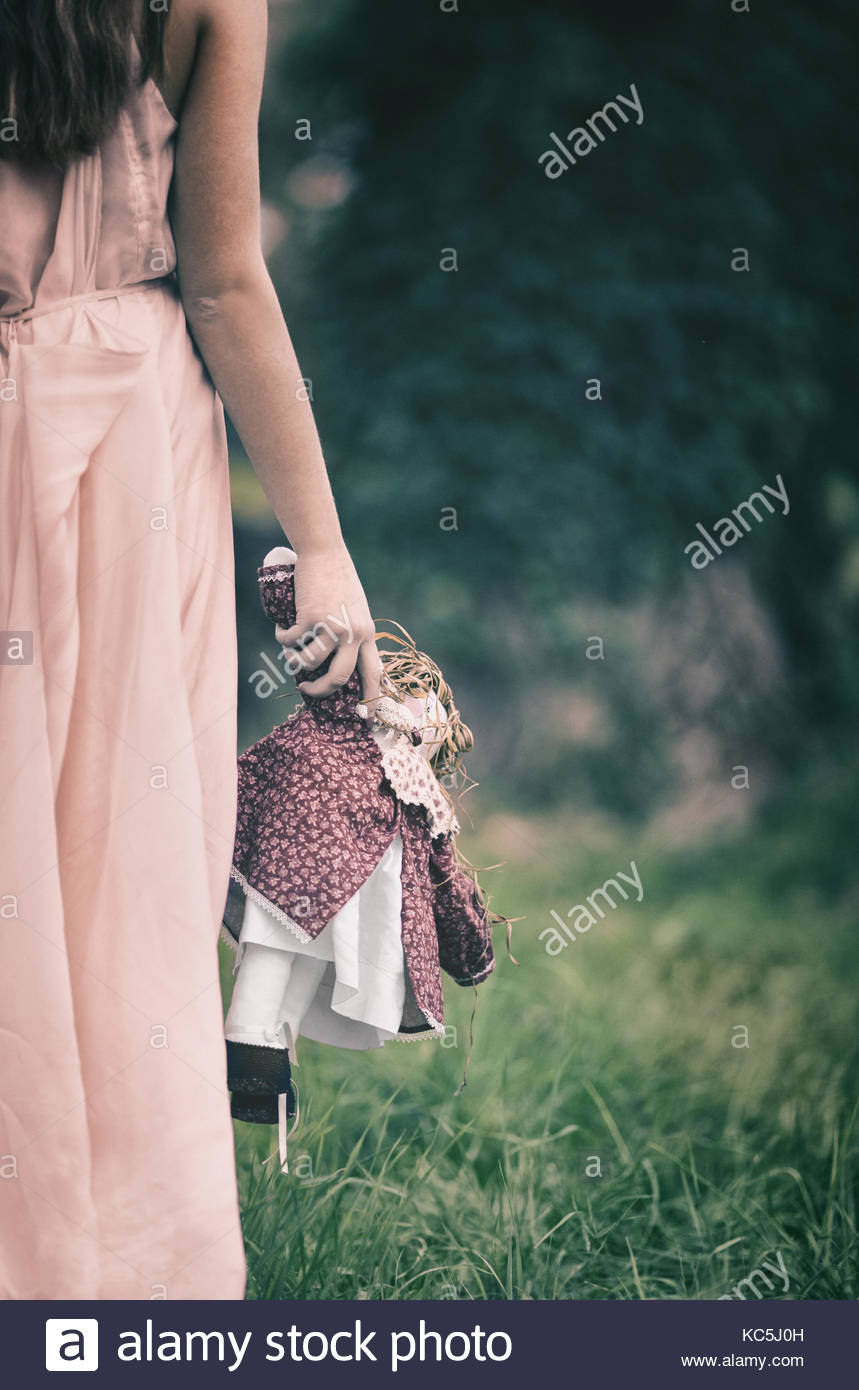 Blonde girl standing by two tall trees covered in ivy, holding a doll - Stock Image