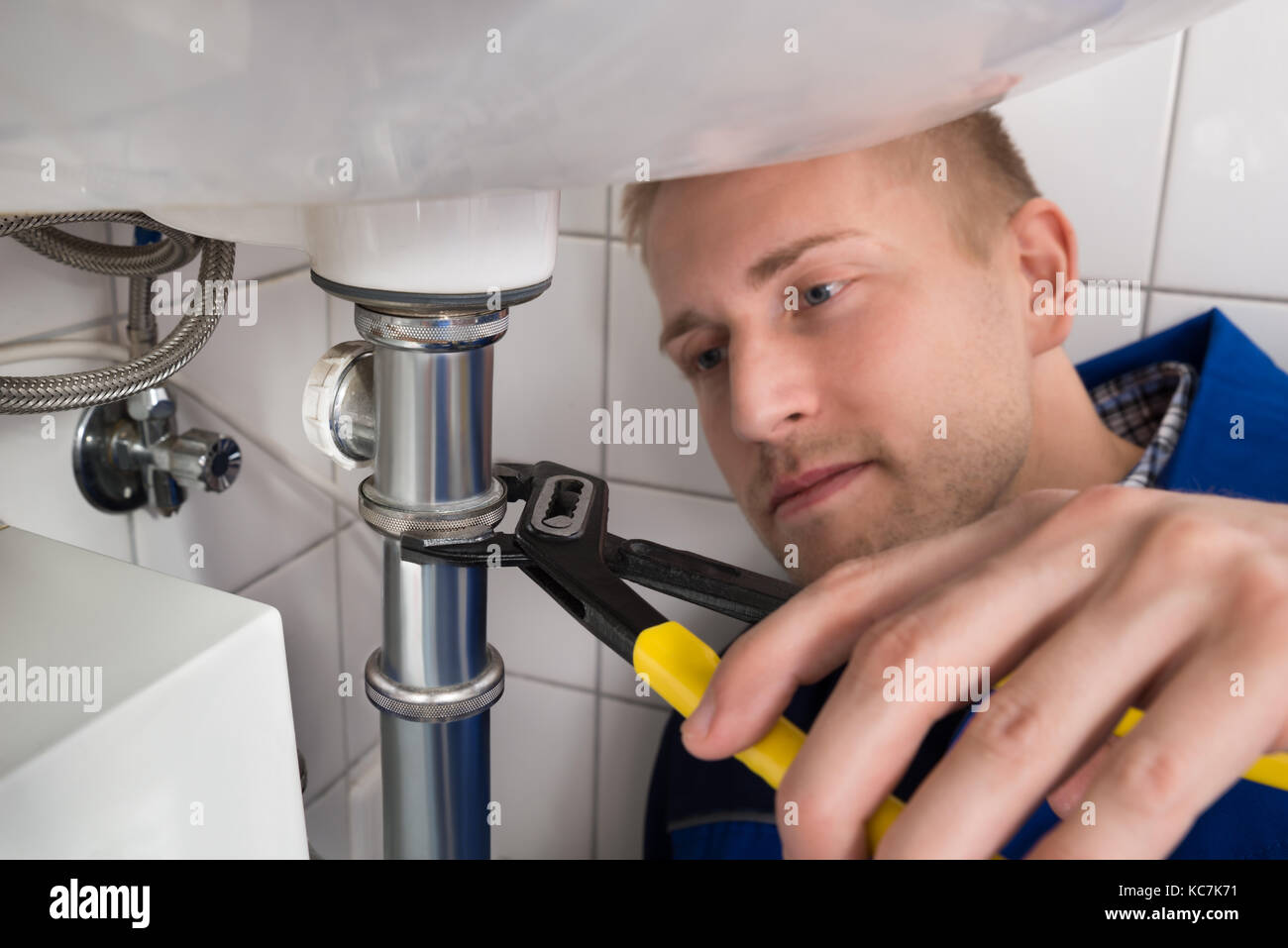 Close-up Of Young Male Plumber Fixing Sink In Kitchen Stock Photo ...