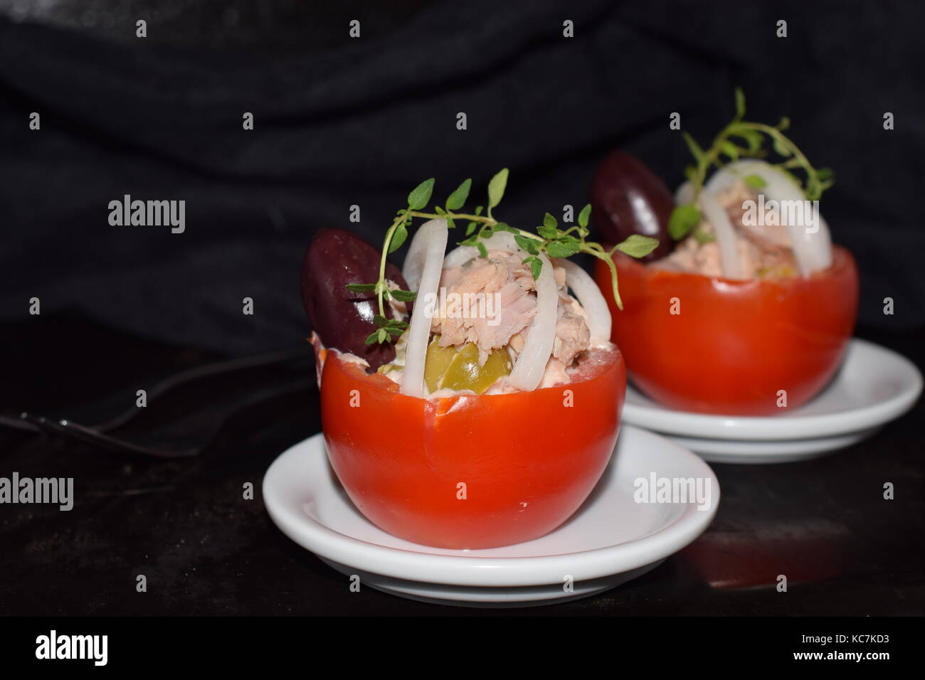 Tomato stuffed with tuna olives and onions. Healthy eating concept. Selective focus - Stock Image