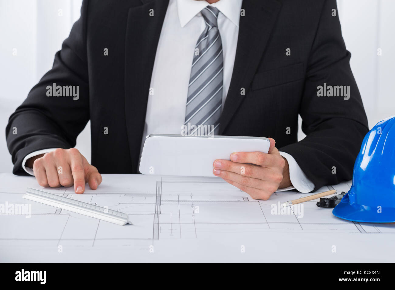 Close-up Of Male Architecture Using Digital Tablet Over Blueprint - Stock Image