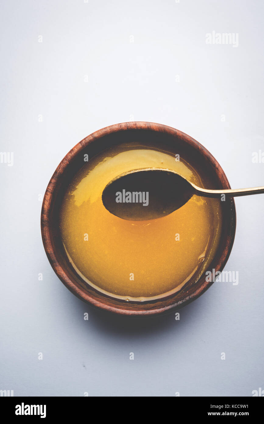 Ghee or clarified butter close up in wooden bowl and silver spoon, selective focus - Stock Image